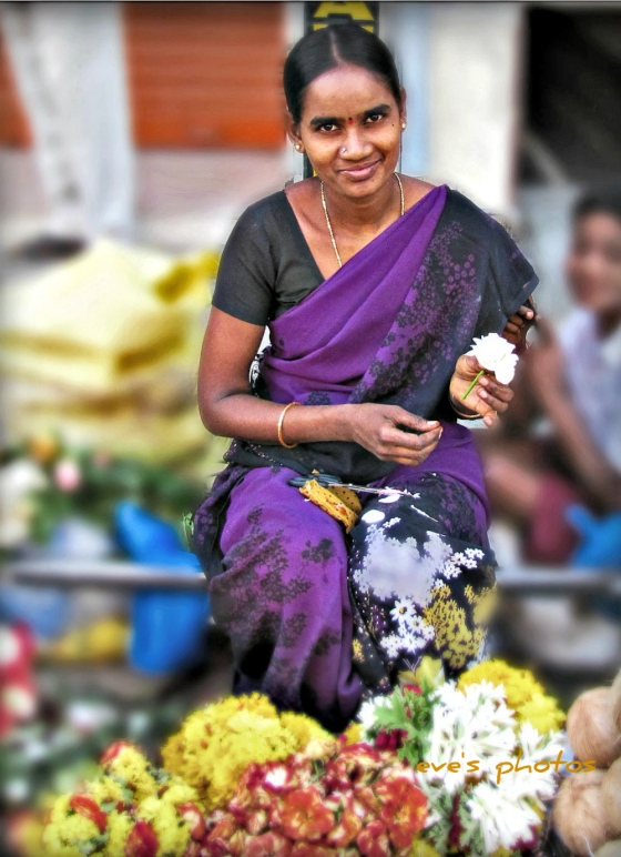 flower lady making garlands for the temple. Puttaparthi, India